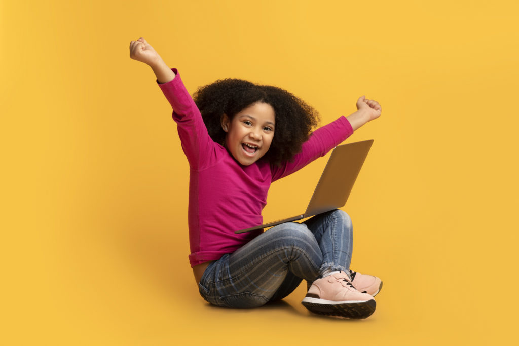 girl celebrates getting one of the free computers for low income families